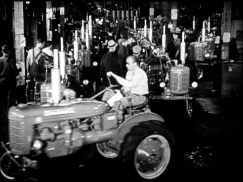vidéos et rushes de tractors people working on tractors parked in rows single tractor driving off production line automobile auto worker guiding car part into position... - michigan