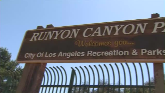 KTLA People working out at Runyon Canyon in Los Angeles Closeup of people hiking Runyon Canyon sign wide shot of canyon