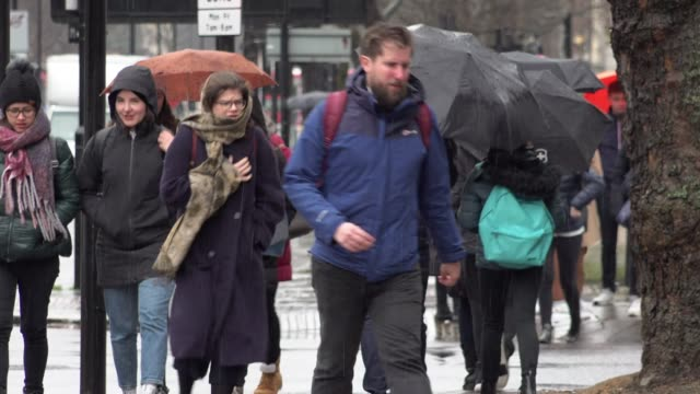 people wrapped up in winter coats use umbrellas to shelter while walking in a heavy downpour of freezing rain as temperatures plummet across the... - winter stock videos & royalty-free footage