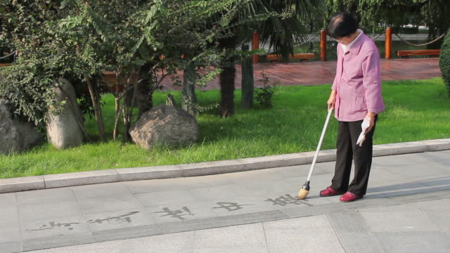 ms people writing calligraphy on pavement in park/xian,shaanxi,china - kalligraphieren stock-videos und b-roll-filmmaterial