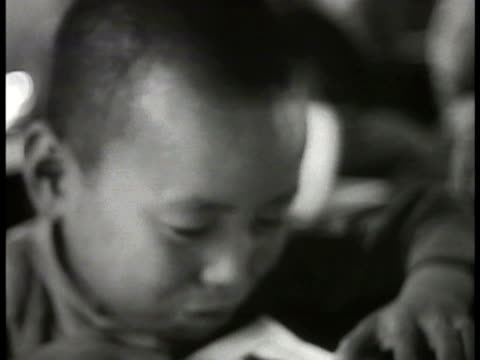 people's faces mancurian chinese mongolian modernization doctor wrapping leg of male w/ gause vs housing for laborers chinese children in class women... - 1935 stock-videos und b-roll-filmmaterial