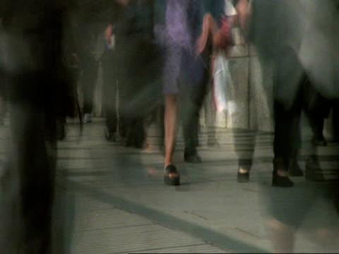 T/L MCU Peoples feet and legs walking down busy city street, London Bridge, London , child pov