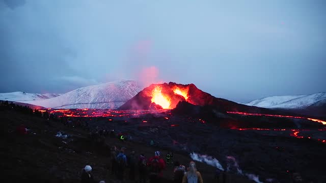 people's figures are illuminated by the glow of the lava field as lava erupts from the volcano's two craters on march 28, 2021 on the reykjanes... - iceland stock videos & royalty-free footage