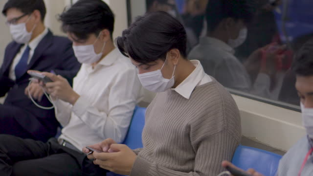peoples in the protection mask use smartphone on subway train - public transport stock videos & royalty-free footage