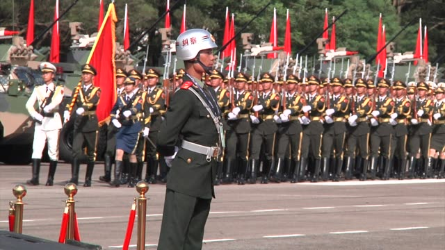 A People's Liberation Army soldier stands at attention while troops march in formation during a visit by Chinese President Xi Jinping at the Shek...