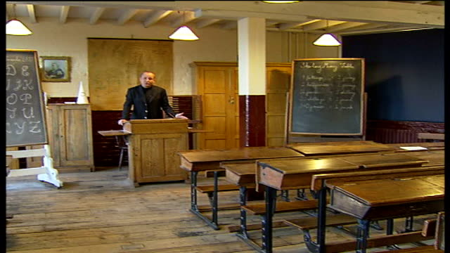 juniper crescent play project / ragamuffin room; int reporter to camera in museum display of victorian classroom - 19th century stock videos & royalty-free footage