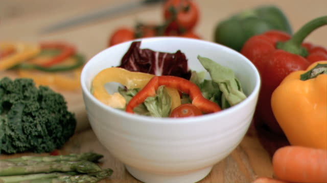 pepper slice dropping into bowl in super slow motion - オレンジピーマン点の映像素材/bロール