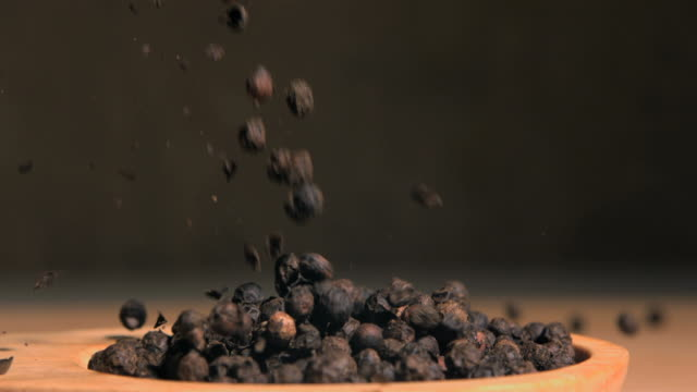 vídeos de stock e filmes b-roll de peppercorns spread in super slow motion in a wooden spoon - pimenta do reino