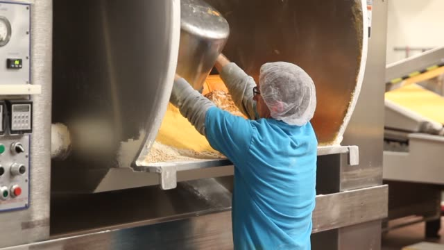pepperidge farm goldfish cracker manufacturing thousands of goldfish move down a conveyer belt and into an oven various machines turn large cheese... - cracker stock videos and b-roll footage