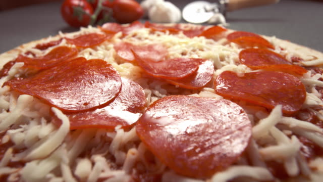 a pepperoni slice falls onto a pizza being prepared with a prepared boboli crust as a base. - mozzarella stock videos & royalty-free footage