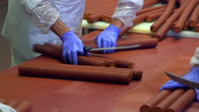pepperoni sliced by factory workers - インスタント食品点の映像素材/bロール