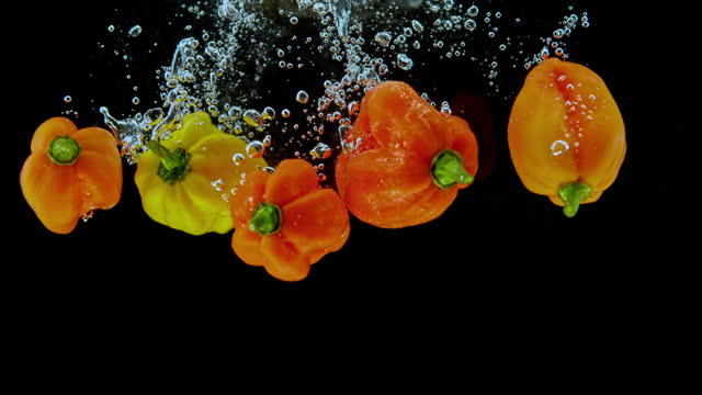 slo mo ld peppers falling into the water - five objects stock videos & royalty-free footage