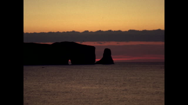 perce rock at sunset, fishing boat in distance - atlantic ocean stock videos & royalty-free footage