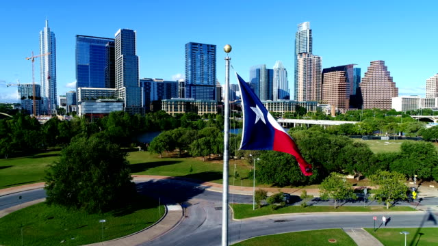 vídeos de stock e filmes b-roll de perfect flyby near texas flag waving in the wind with the austin cityscape skyline in the background - texas