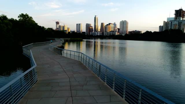 Perfect Sunrise Skyline Cityscape moving forward above Riverside Pedestrian bridge in Austin Texas Swinging over top of bridge