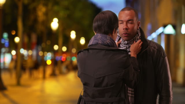 Perfectionist ethnic female adjusts boyfriend's scarf on Champs-Elysees