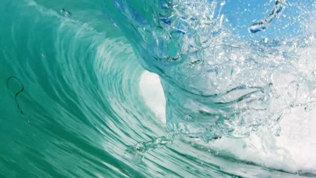 Perfectly detailed beautiful wave POV as wave breaks over camera on shallow sand beach in the California summer sun. Shot in slowmo on the Red Dragon at 300FPS.