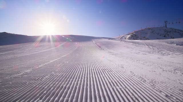 DS Perfectly groomed morning ski track lit by sun