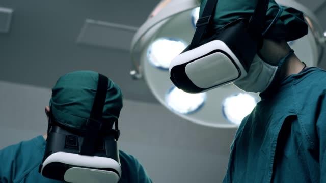 vídeos y material grabado en eventos de stock de realizar cirugía de vanguardia en el hospital de alta tecnología. médicos y asistentes trabajando en quirófano. - cirujano