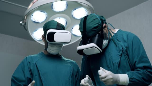 stockvideo's en b-roll-footage met voer state of the art surgery uit in high tech ziekenhuis. artsen en assistenten die in operatiekamer werken. - chirurgie