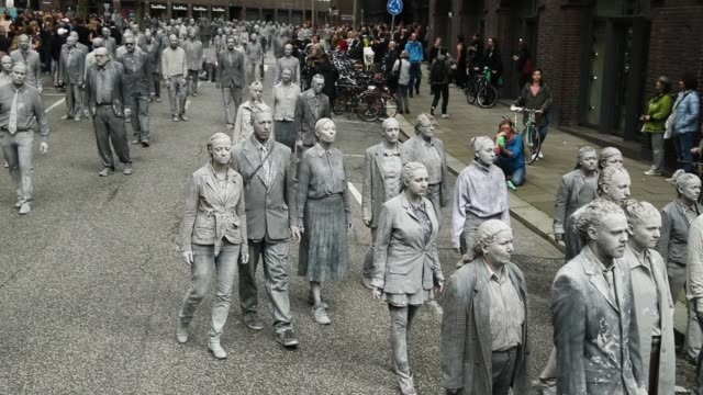Performance artists covered in clay to look like zombies walk trancelike through the city center during a preliminary performance on July 5 2017 in...