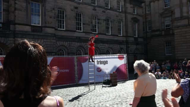 vídeos de stock, filmes e b-roll de a performer at the fringe festival on a square is performing for an audience on a ladder holding up juggle clubs - festivaleiro