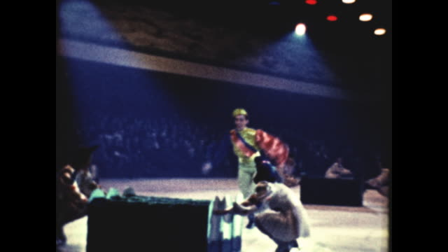 performer dressed in red and green jumping over obstacles with one leg on ice - on one leg stock videos & royalty-free footage