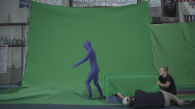 performer in blue body suit does a backflip onto green block - movie studio stock videos and b-roll footage