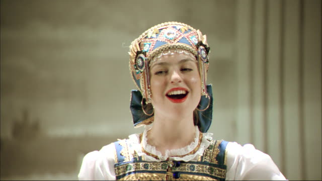 A performer wearing traditional clothing sings on a stage.