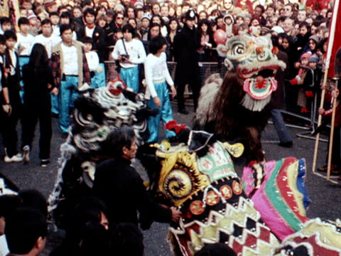 performers dressed as ornamental lions dance for the crowds in london's chinatown during the chinese new year celebrations - chinatown stock videos & royalty-free footage