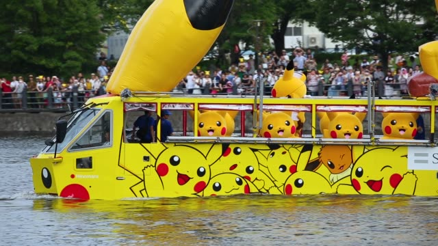 performers dressed as pikachu, a character from pokemon series game titles, ride on amphibious buses during the pikachu outbreak event hosted by the... - pokémon stock videos & royalty-free footage