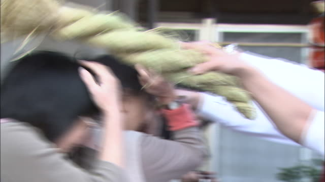 performers dressed as sinister lions tap spectators on the head with rice-straw ropes during the gatchi festival in japan. - shimenawa stock videos & royalty-free footage