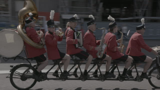 performers on long bike ride down amsterdam street singing and playing instruments - netherlands stock videos & royalty-free footage