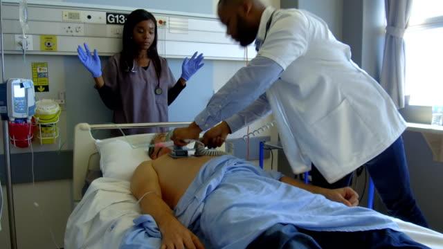 vídeos de stock, filmes e b-roll de realizando cpr em um paciente grave - defribilador