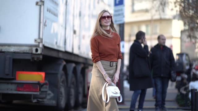 pernille teisbaek wears an orange top with a golden necklace, a beige skirt, a white chloe bag, burgundy leather boots, outside chloe, during paris... - street style stock videos & royalty-free footage