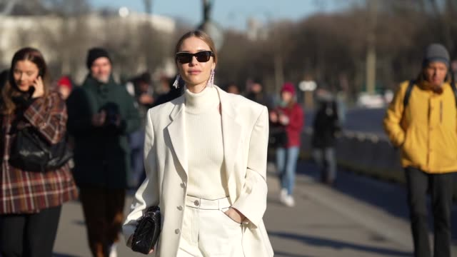 stockvideo's en b-roll-footage met pernille teisbaek wears sunglasses earrings a white turtleneck pullover an oversized blazer jacket a chanel quilted bag flare pants pointy shoes... - coltrui