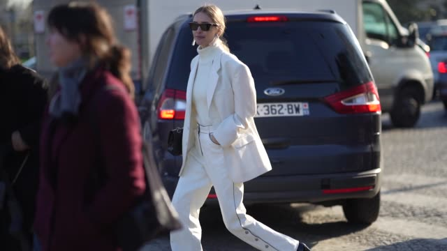 stockvideo's en b-roll-footage met pernille teisbaek wears sunglasses earrings a white turtleneck pullover an oversized blazer jacket a chanel quilted bag flare pants pointy shoes... - gepunt