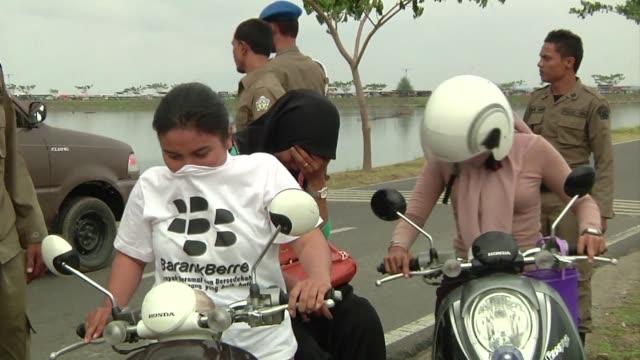 vídeos de stock, filmes e b-roll de perseguidas por no usar velo o sentarse con una pierna a cada lado en motocicleta las mujeres indonesias de la region de aceh consideran que las... - véu