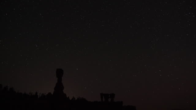 Perseid meteors along with satellites and lights from passing planes streak across the sky above the hoodoos named Thor's Hammer and the Three...
