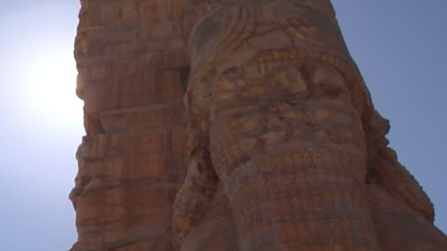 persepolis lowangle view of the face of one of the massive stone lamassu protective deities decorating the gate of all nations in the ruins of the... - persepoli video stock e b–roll