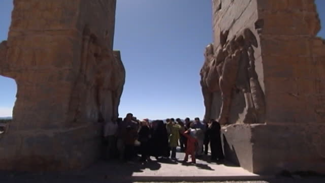 persepolis view of tourists admiring the massive stone lamassu protective deities decorating the gate of all nations in the ruins of the ancient city... - persepoli video stock e b–roll
