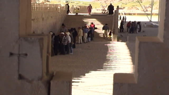 persepolis view of tourists looking at reliefs carved into the walls of the apadana palace in persepolis the city dates to 515 bce and is a unesco... - persepoli video stock e b–roll