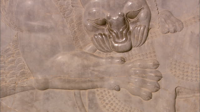 a persian bas-relief depicts a mythical lion biting another creature. - bas relief stock videos & royalty-free footage