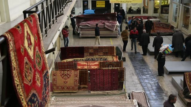 Persian carpets hang from railings and sit in piles as vendors wait for customers inside the rug bazaar in Tehran Iran on Monday Jan 15 2018
