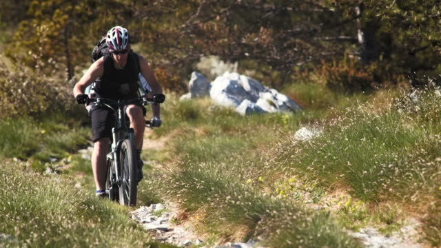 vídeos de stock, filmes e b-roll de hd: persistentes ciclistas de montanha de bicicleta, íngremes - colina acima