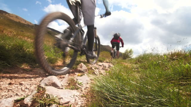 hd: persistent mountain bikers on heathland track - uphill stock videos & royalty-free footage