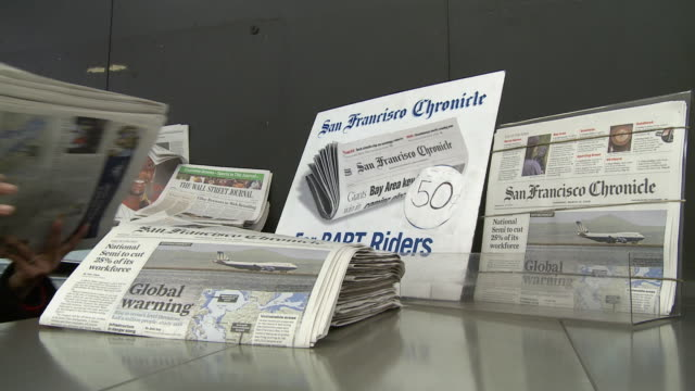 vídeos de stock, filmes e b-roll de cu person arranging newspapers at news stand, san francisco, california, usa / audio - primeira página de jornal