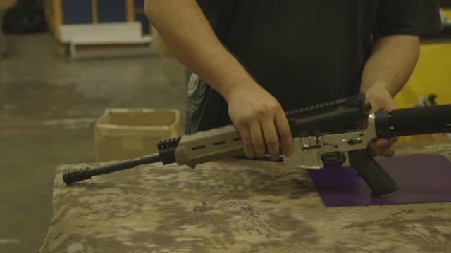 person assembles handmade rifle, medium shot - gun stock videos & royalty-free footage