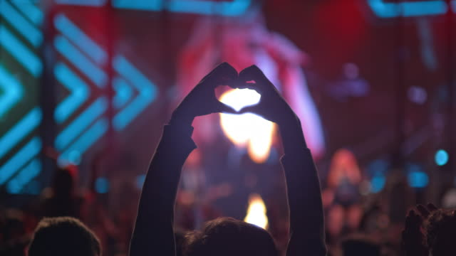 slo mo person at concert making a heart with hands - hand raised stock videos & royalty-free footage
