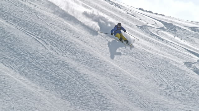 vídeos y material grabado en eventos de stock de slo mo person backcountry skiing down sunny mountain - nieve en polvo